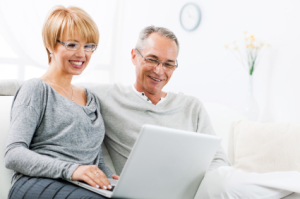 Portrait of a smiling mature man and woman using a laptop together. [url=http://www.istockphoto.com/search/lightbox/9786786][img]http://dl.dropbox.com/u/40117171/couples.jpg[/img][/url]